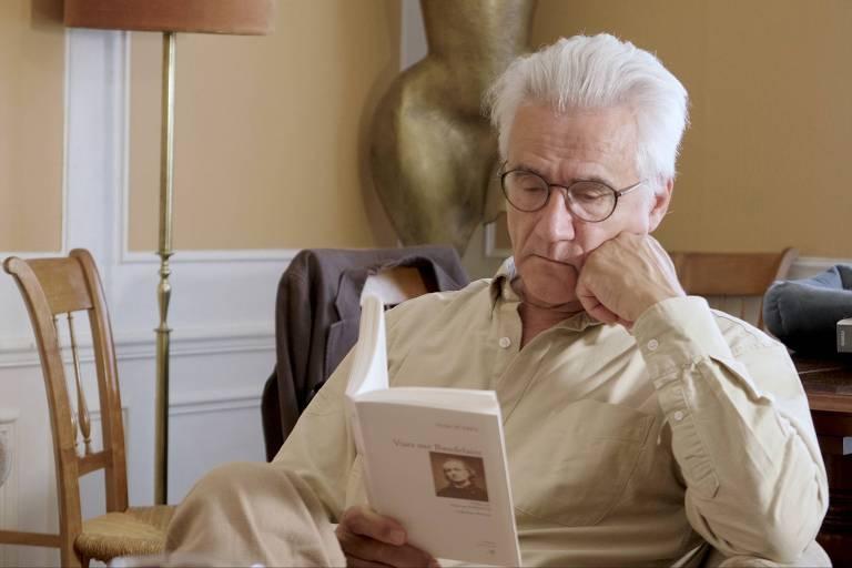 homem branco de cabelos brancos e óculos sentado lendo