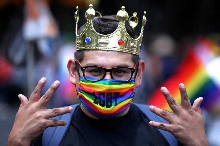 """Um homem de coroa na cabeça, óculos e uma máscara no rosto onde tem escrito a sigla """"LGBT"""" durante a parada do orgulho LGBT+, em Guaralajara, no México"""