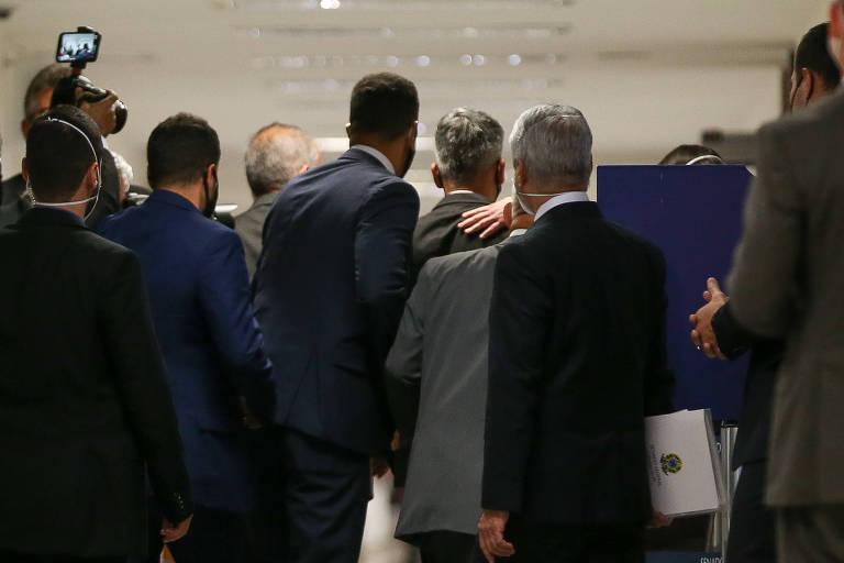 Policiais do Senado conduzem Roberto Dias (de costas, com uma mão em suas costas)