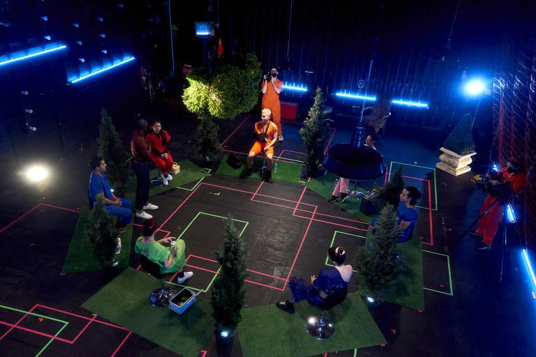 Palco de teatro com marcações com linhas no chão e pedaços de piso falso de grama; atores estão sentados em roda, em cadeiras