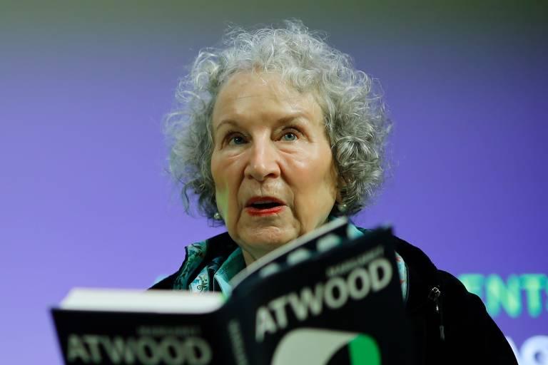 Margaret Atwood, mulher branca de cabelo curto e encaracolado branco lendo um livro de 'O Conto de Aia'