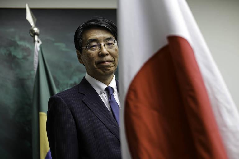 Homem de terno atrás de bandeira do Japão, com bandeira do Brasil ao fundo