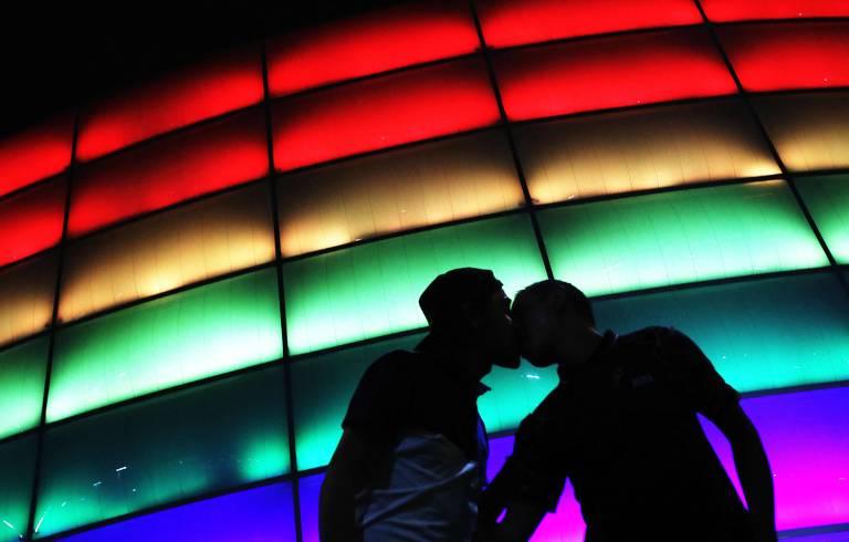 Dois homens se beijam diante de uma parede de luzes nas cores do arco-íris durante o Dia Internacional do Orgulho LGBT, em 2021.