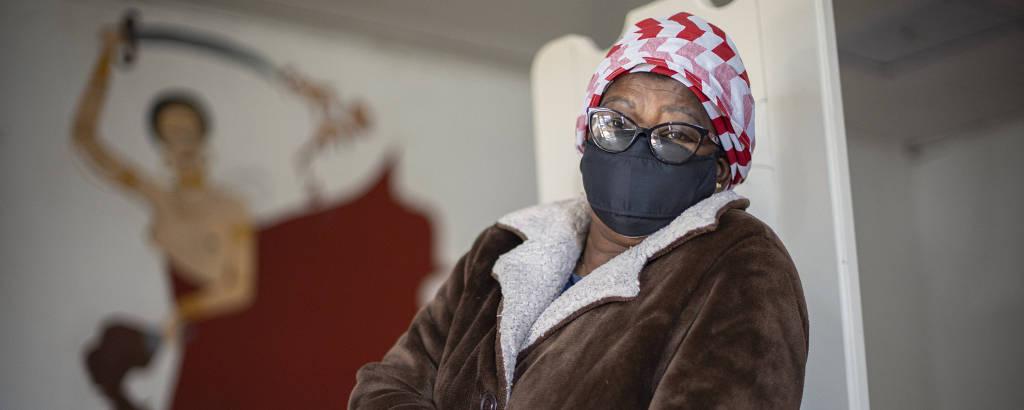 Mulher negra de óculos, lenço vermelho e branco na cabeça e casaco marrom em frente a parede com pintura de orixá
