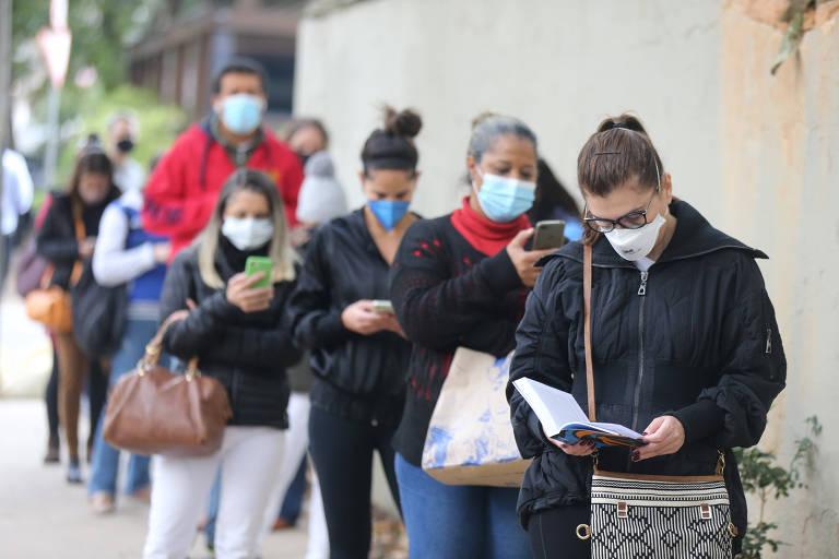 Fila de pessoas agasalhadas e usando máscara