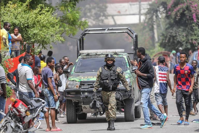 Haitianos se reúnem do lado de fora da delegacia de polícia de Petionville, onde os supostos assassinos do presidente do país estão detidos