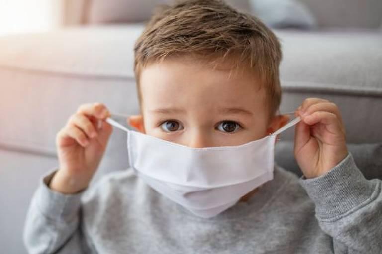 Uma criança segura pelas alças uma máscara branca e a leva em direção a boca.