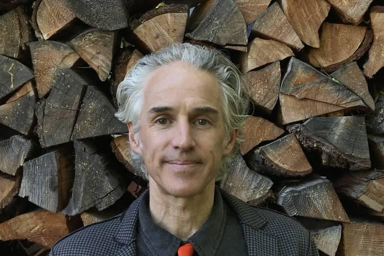 Jules Boykoff, de frente, com roupas pretas e uma gravata vermelha. Ao fundo, é possível ver toras de madeira cortadas e empilhadas