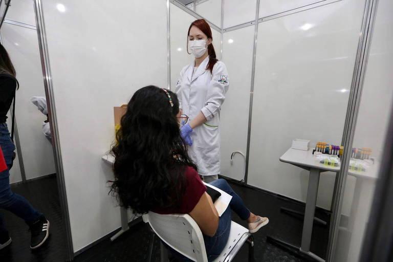 Na imagem, uma mulher está sentada e de costas em uma sala. Na frente dela, uma profissional da saúde de máscara, jaleco e luvas está em pé.