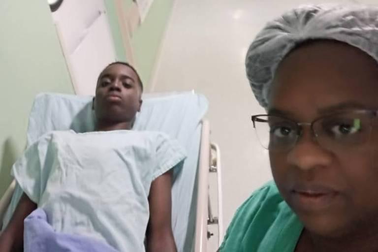 mulher de roupa verde e touca posa ao lado de filho, na maca, em hospital