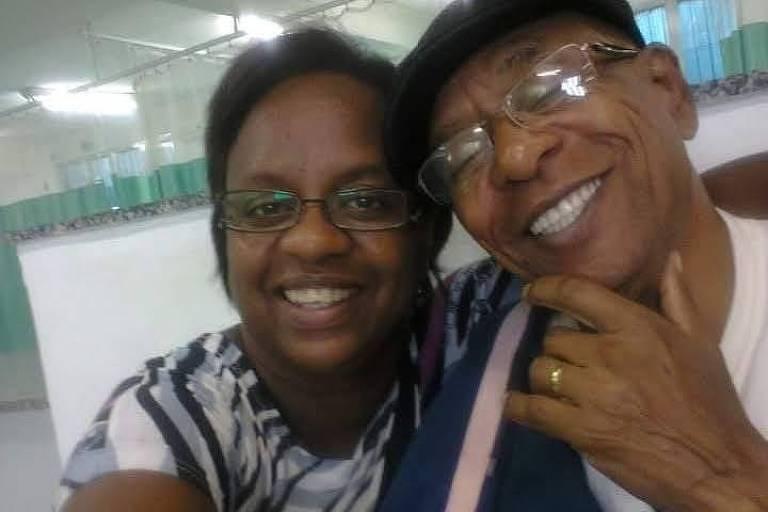 mulher negra sorri ao lado de senhor negro de óculos e boina