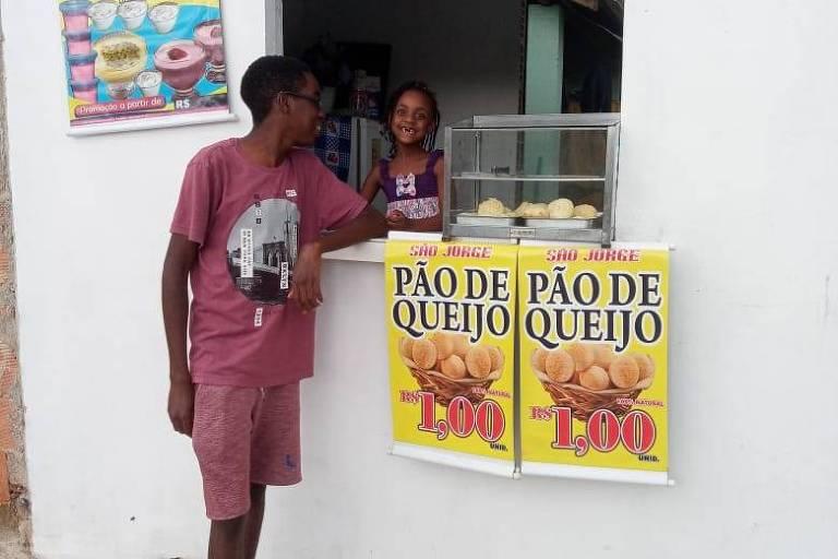 duas crianças posam em frente a uma janela de casa com cartaz sobre venda de pães de queijo
