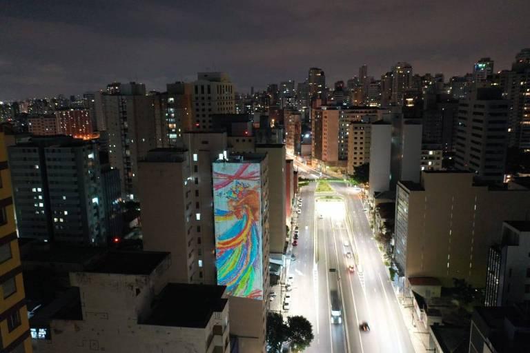 Projeção mostra obra criada por Jean Wyllys para a mostra 'Brasileires' em fachada de prédio; desenho exibe uma mão que segura várias fitas coloridas