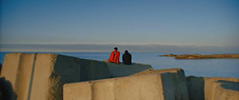 Duas pessoas aparecem sentadas em pedras e, ao fundo, vê-se o mar