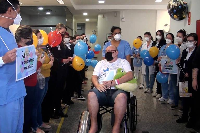 De cadeira de rodas, Marcos Elias Jacobsen acena para funcionários do hospital após deixar internação. Médicos e enfermeiros seguram balões e cartazes.
