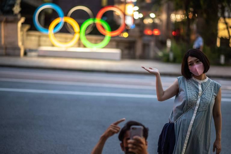 Casal posa em frente aos anéis olímpicos de Tóquio, no distrito de Nihonbashi