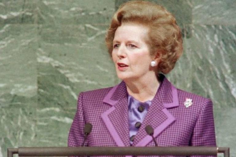 mulher branca, loira de cabelos curtos e penteados de forma elegante discursa diante de microfone