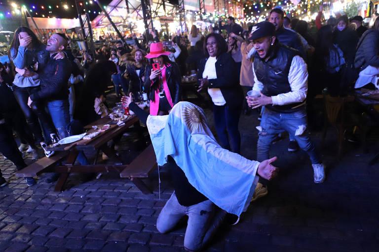 Em primeiro, plano, torcedor está ajoelhado e tem uma bandeira da argentina sobre a cabeça; atrás dele, pessoas comemoram a vitória