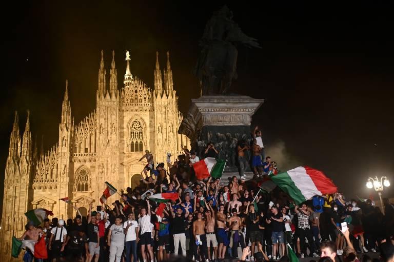 Multidão com bandeiras da Itália em frente a igreja antiga
