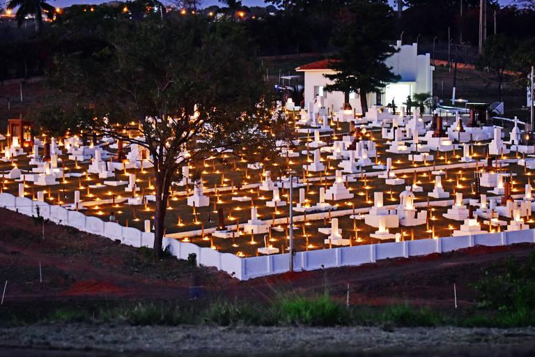 Imagem aberta mostra as velas acesas sobre as lápides