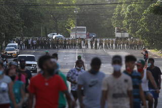 Demonstrators walk away from army soldiers blocking a road during a protest against and in support of the government in Havana