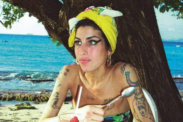 amy sentada em praia de biquini