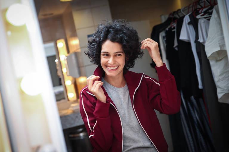 Maria Flor é branca, magra e está de cabelo curto, cacheado e escuro. Ela veste uma camiseta cinza e um casaco vinho com listra branca nas mangas. A sua direita na foto há uma arara de roupas
