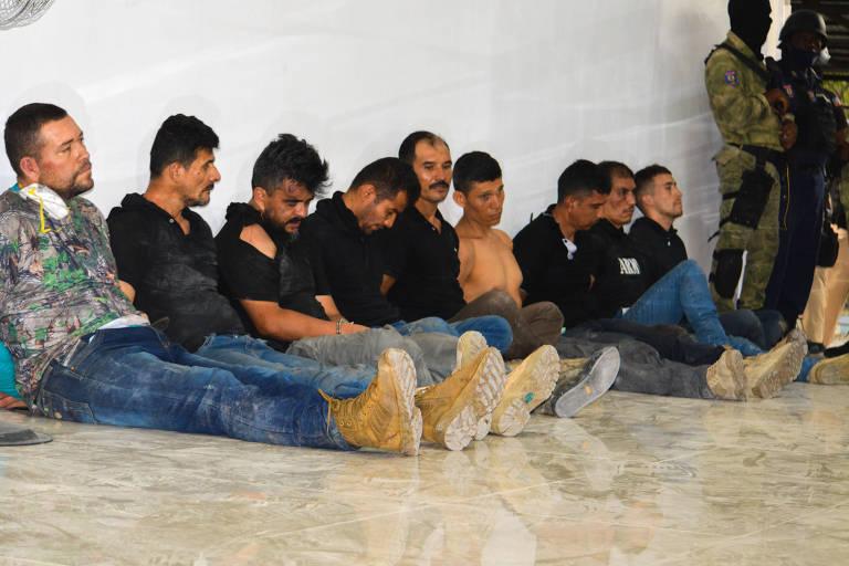 Nove homens de calça jeans e camiseta preta, camuflada verde (o homem da ponta esquerda está vestindo uma camiseta camuflada), ou sem camisa (o quarto homem da direita para esquerda está sem camisa) sentam no chão encostados na parede. À sua direita, dois guardas armados vestidos de roupas camufladas. A parede é branca e o chão é bege.