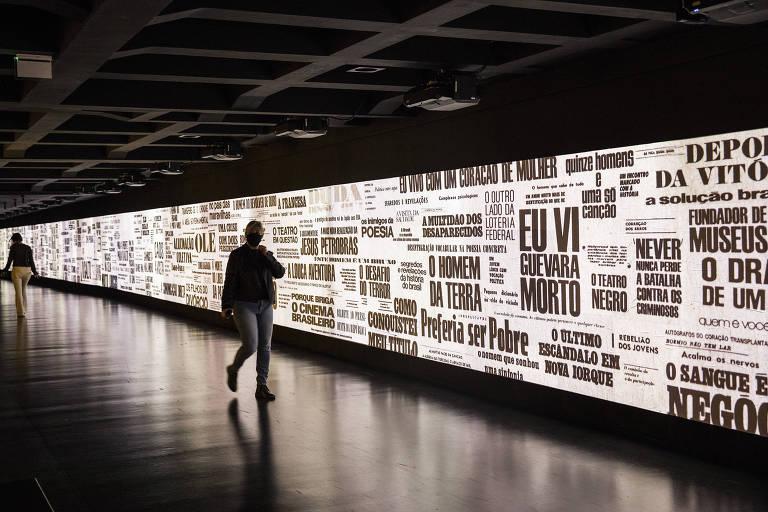 Pessoas caminham por corredor que exibe projeções em vídeo