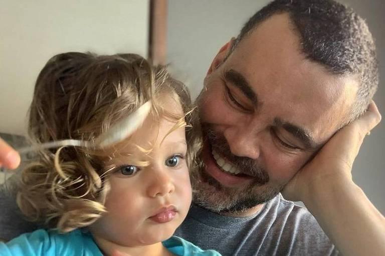 Homem branco de cabelo grisalho e bebê loiro dos olhos azuis