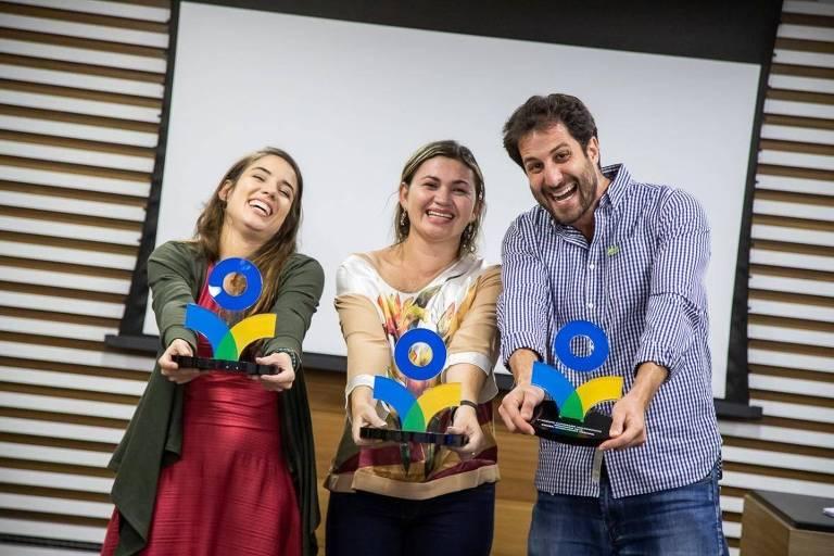 duas mulheres brancas e um homem branco seguram um prêmio em mãos