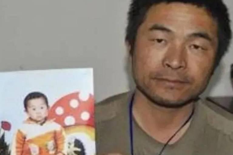 Homem asiático segurando a foto de um bebê