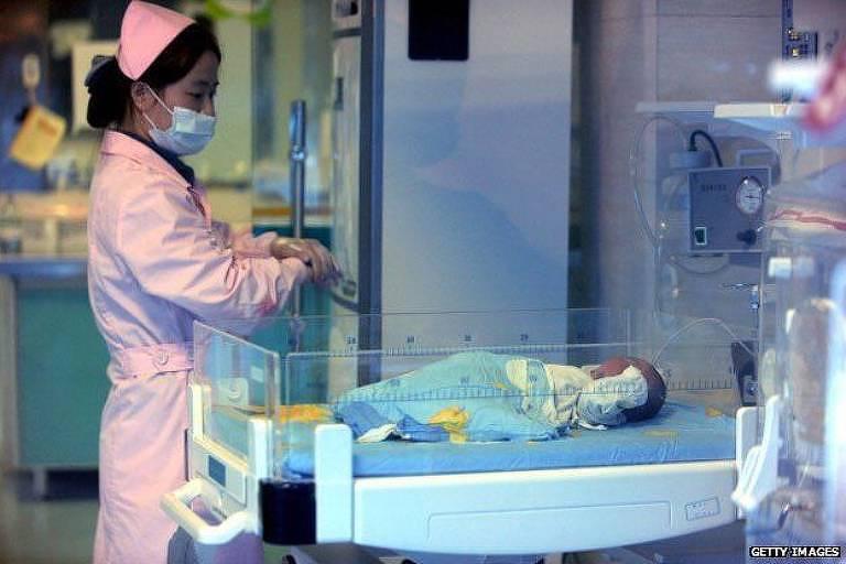 Mulher vestida de rosa e com máscara cirúrgica cuidando de um bebê