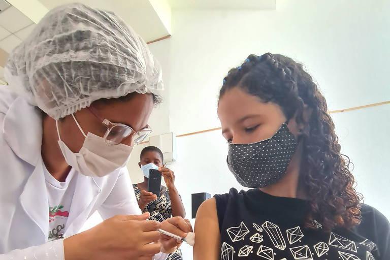 mulher aplica vacina no braço de uma adolescente