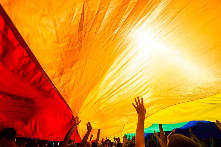 pessoas estão embaixo de enorme bandeira do arco-íris