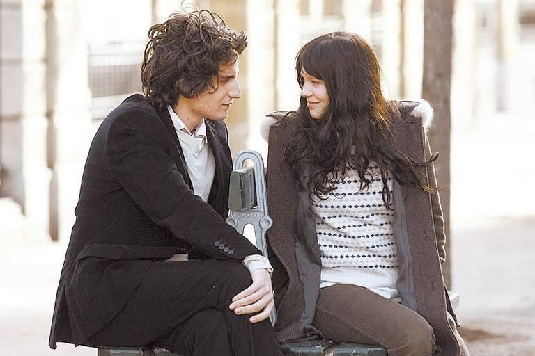 homem e mulher brancos de cabelos escuros se olham sentados em um banco