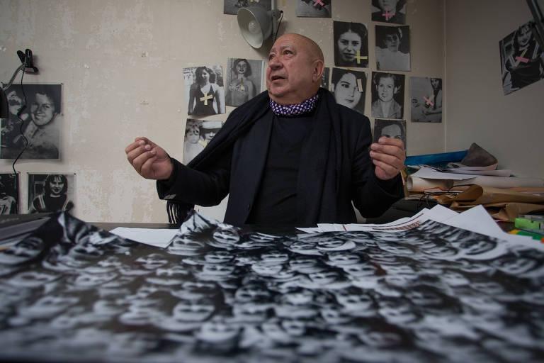 homem branco careca de rosto redondo usando casaco preto e cachecol branco e preto diante de mesa cheia de recortes de papeis com rostos; ele está de braços abertos e parece que fala