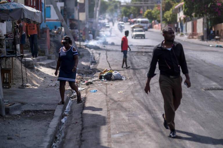 Haitianos caminham em rua de Porto Príncipe após pneus serem incendiados durante protestos