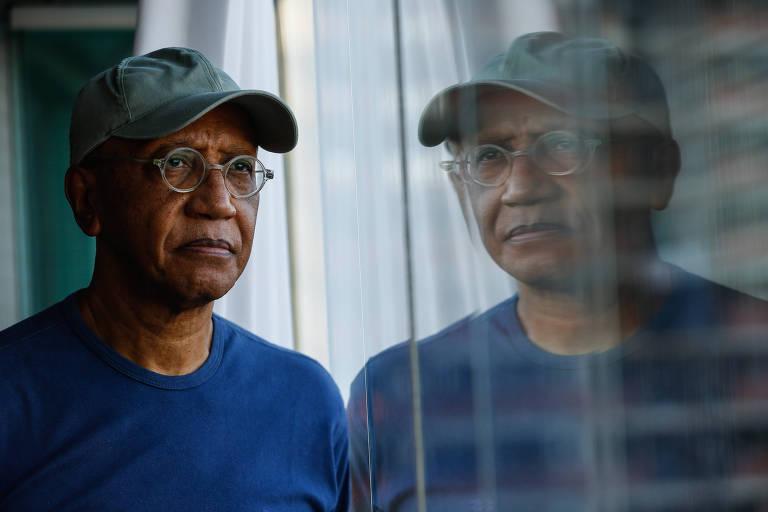 homem negro, de camiseta azul e boné, olha pela janela
