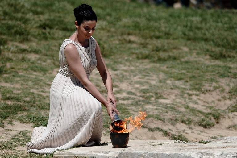 Atriz grega Ino Menegaki, vestida como uma alta sacerdotisa, acende a tocha olímpica dos Jogos de Londres-12 no templo de Hera, na cidade de Olimpia (GRE), ato que é tradição na abertura dos Jogos