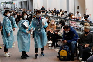 Officials prepare to administer COVID-19 antigen test to U.S. gymnastics team at Narita Airport ahead of Tokyo 2020 Olympic Games, in Narita