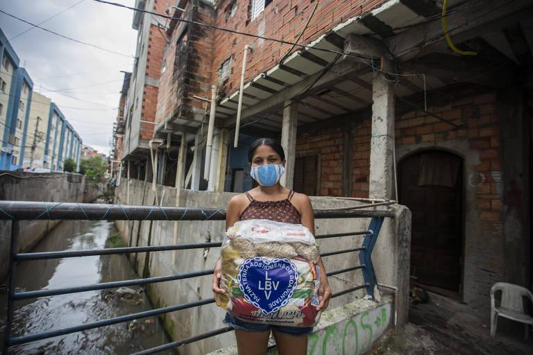 mulher segura cesta de alimentos em ponte dentro de comunidade