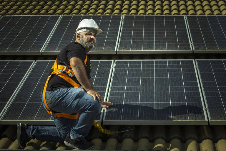 Homem de capacete e equipamento de segurança instalando painéis de energia solar, que são quadrados escuros, em um telhado