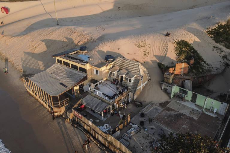 Imagem aérea mostra areia das dunas invadindo casas