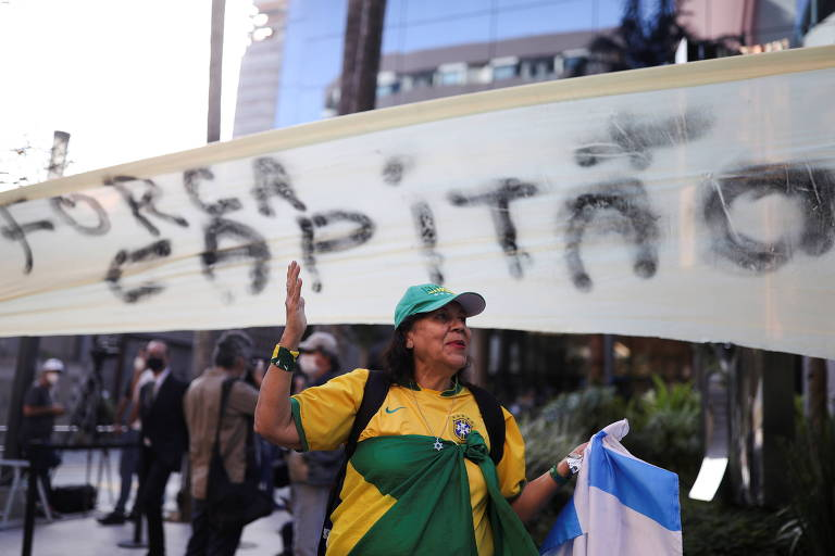 """Apoiadora de Jair Bolsonaro ergue a mão embaixo de faixa em que se lê """"força capitão"""", em frente ao hospital onde o presidente está internado em São Paulo"""