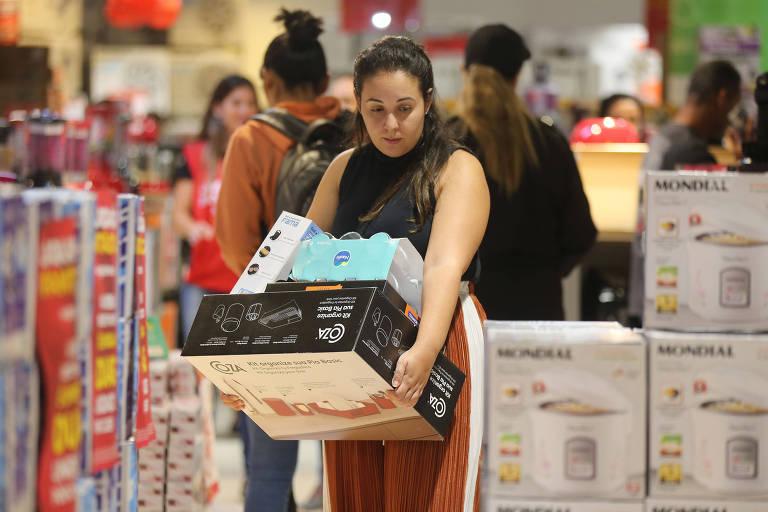 Mulher carrega compras em meio a produtos em loja