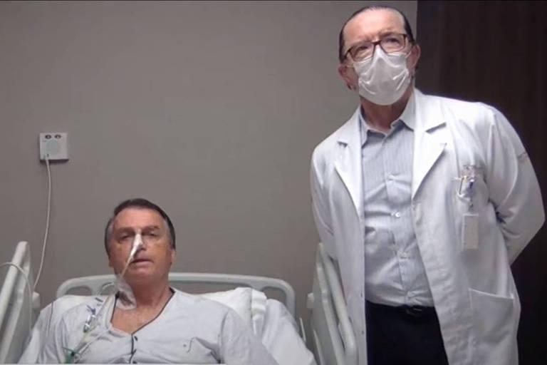 O presidente Jair Bolsonaro e seu médico, Antonio Macedo, durante entrevista ao apresentador Sikêra Jr. nesta quinta (15) no hospital onde está internado em SP