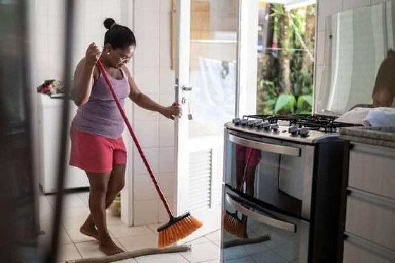 Mulher limpa a casa com uma vassoura
