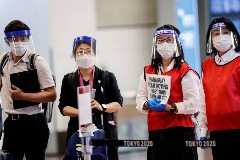 Quatro funcionários do aeroporto de Haneda, no Japão, usando máscaras de proteção e face shield, aguardam chegada de atletas  no saguão