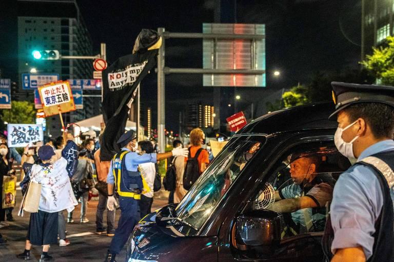 Policia observa manifestantes ao lado de um carro